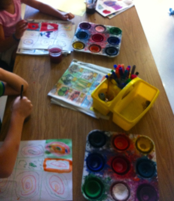 A very blurry picture of some 1st graders painting
